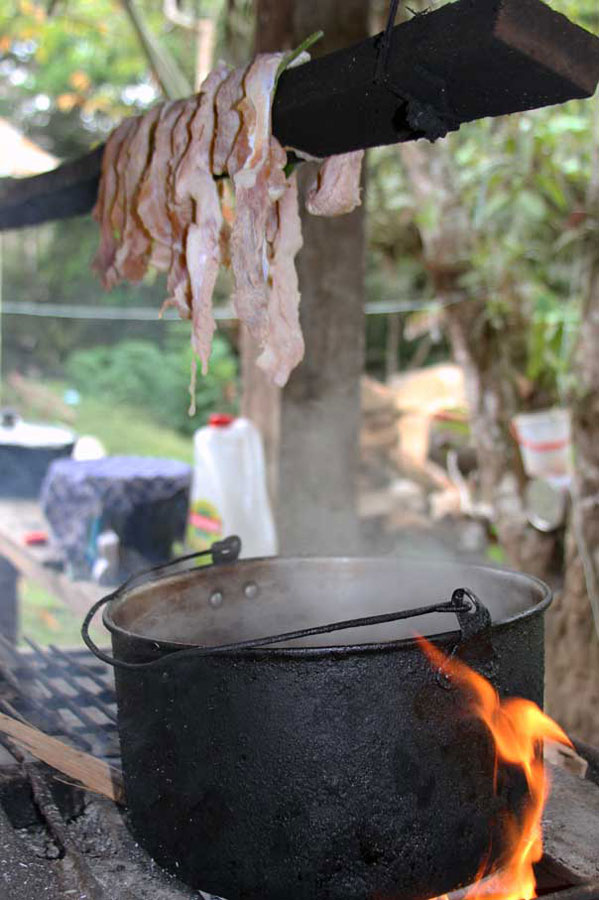 Pork hangs above an open fire and cooking pot in a traditional outdoor kitchen. This method of smoking the meat results in a chewy, bacon-like flavor.