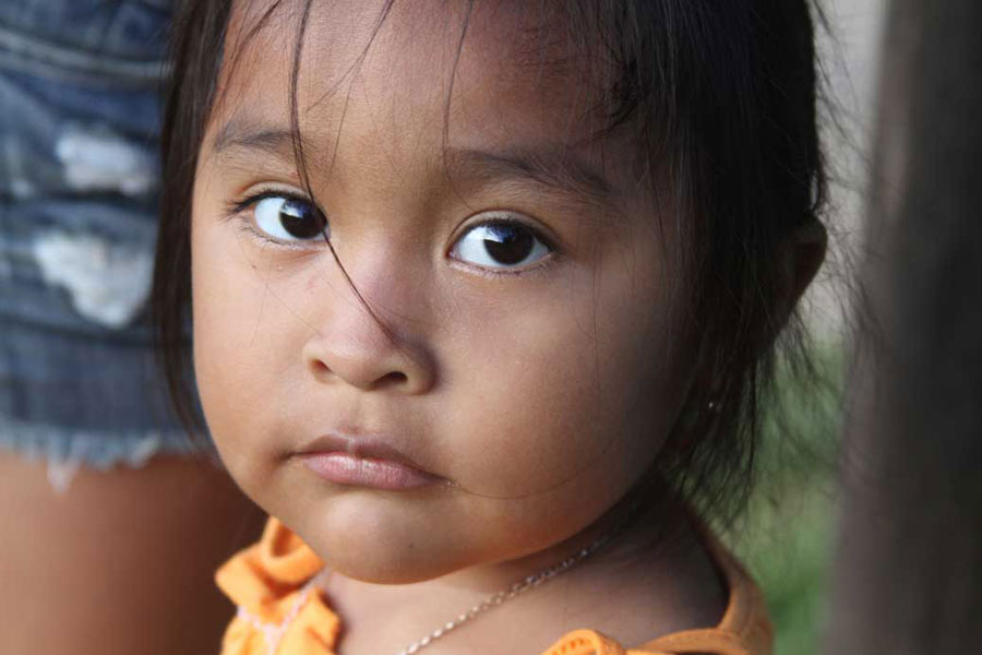 Two-year-old Donna looks up from beside her cousin in her family's outdoor kitchen near the village center of Boruca.