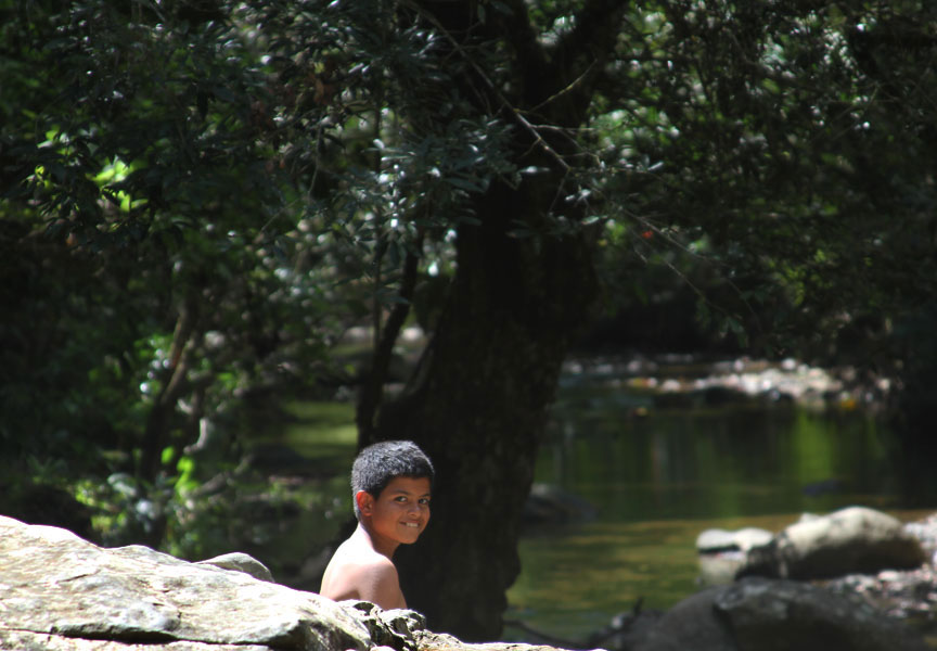 A boy sits near the river outside the village center of Boruca. This swimming hole is called Mambram, and is the setting for the local legend of The Two Sisters. Villagers hike to this spot to swim on hot days.