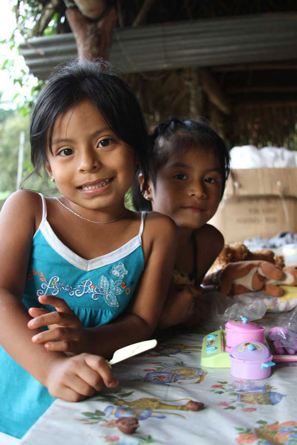 Two sisters play under their family's traditional rancho. Some natives are saddened that children are spending more time watching television rather than listening to elders tell stories about the Boruca identity.
