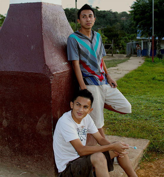 Two teens relax beside the large cross that towers over the churchyard and village of Boruca.