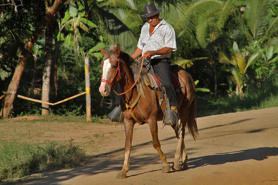 A man rides a horse down the street just across from the museum in Boruca. The museum dedicated to indigenous culture is located near the village center and is a common stop for day visitors.