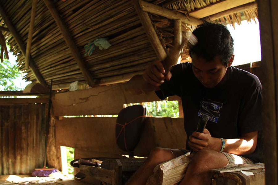 An artisan carves a traditional Diablitos mask in his thatch-roofed workshop in Boruca. The craft is taught to children as soon as they are old enough to hold the tools. Since the efforts to revive the faltering traditions, mask-making is now taught in the local school.