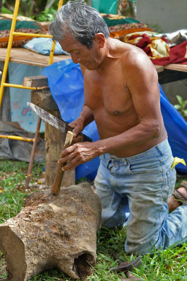 A man carves a piece of wood to repair a broken tool. Living in such a remote village, many Boruca rely on their own ingenuity to handle everyday problems such as this.