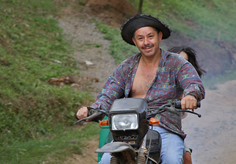 Oscar Morales-Leiba drives a motorcycle down the road as his daughter rides on the back. Morales-Leiba teaches the Boruca language to school children as part of ongoing cultural preservation efforts.