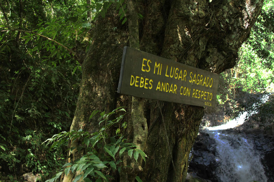 "As water surges down the mountain of Cuasrán, a sign reads, ""It is my sacred place, you should go with respect."" Boruca legends says that the mountain and waterfall are the home of Cuasrán and should be treated as sacred. The spirits of those faithful to Cuasrán and the land go to the waterfall to unite with the spirit."