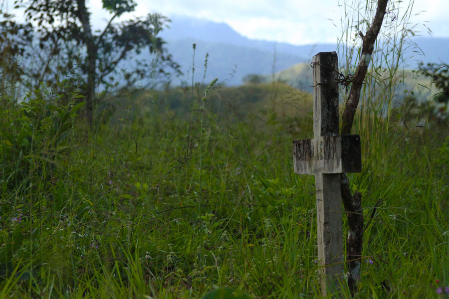 A cross marks a grave in the cemetery just outside the center of Boruca. Located on a hilltop, the cemetery is surrounded by picturesque views of neighboring mountains. In fact, some believe that the spirits of those who are connected to the land go to the mountain of Cuasrán after death.