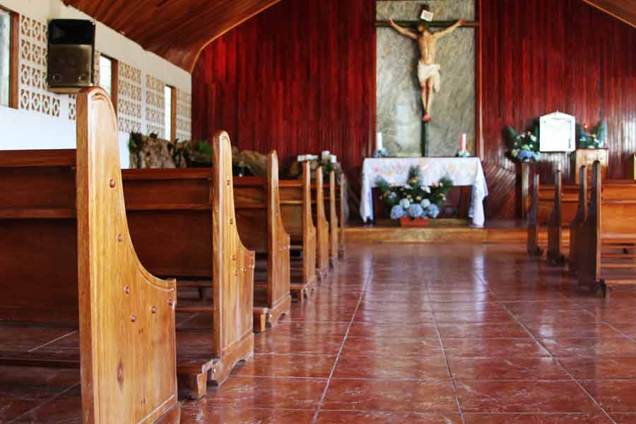 Pews sit empty as a crucifix hangs inside Boruca's only church. Although empty now, Mass, spoken in part Boruca language and part Spanish, is held daily in this small village.