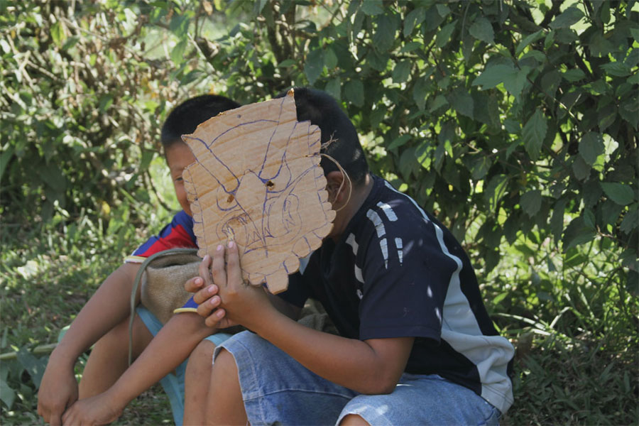 Sitting outside of their home, two boys play with a cardboard mask, mimicking that of an authentic Diablitos mask.